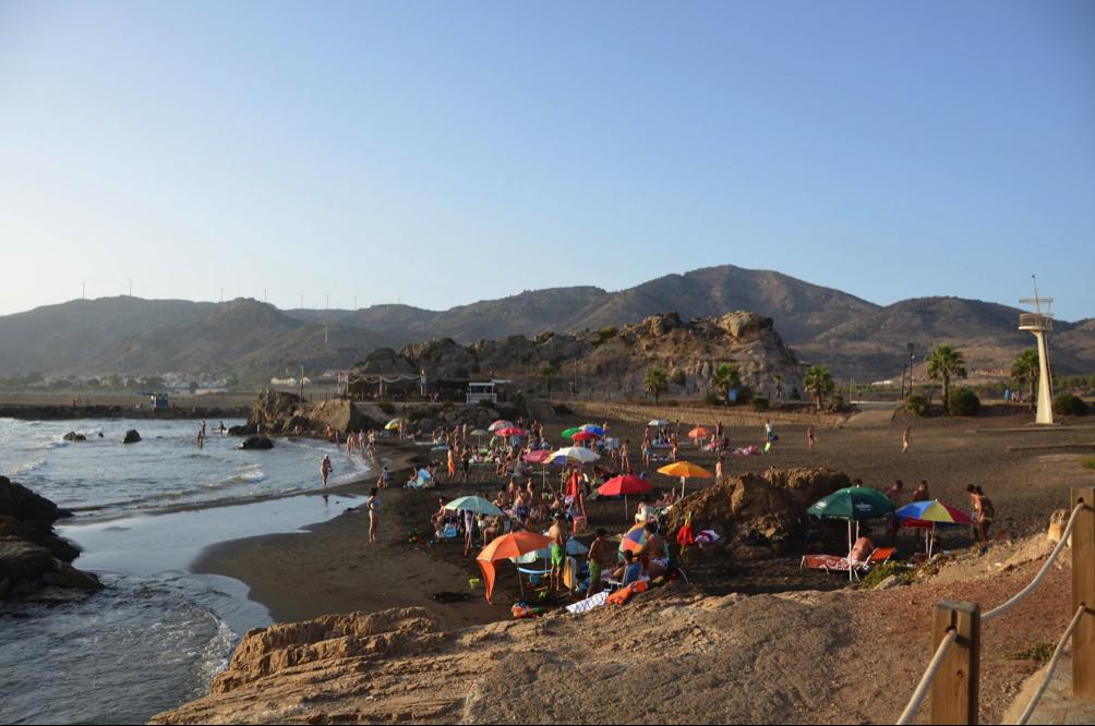 """Personas """"disfrutando"""" de la tóxica playa de Portmán. En la imagen se aprecia que la playa está habilitada con puesto de socorro, accesos mediante pasarelas y chiringuito, entre otros servicios."""